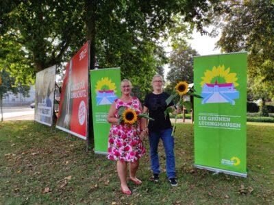 Foto v.L.n.R.: Anke Brandmeier, Lars Reichmann - auf dem Bild sieht man, wie die beiden am Kreisverkehr vor Roll-Ups und mit Blumen in der Hand stehen.
